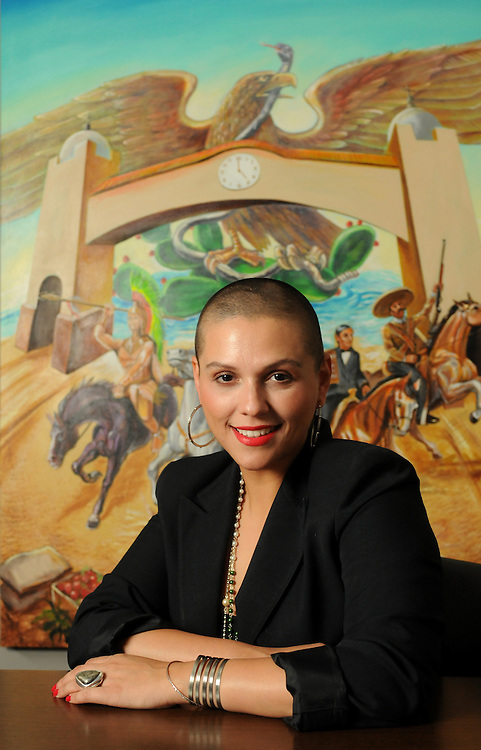 Little Village Chamber of Commerce Executive Director Nilda Esparza is photographed near a painting in her office by Chicago artist Oscar Romero.