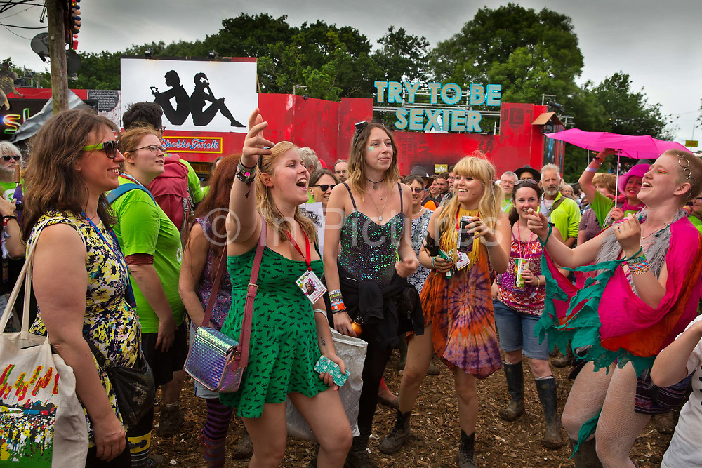 Women singing outside 'The Sisterhood', Glastonbury's first women-only space, opened by Emily Eavis to honour the life of murdered MP Jo Cox in the Shangri La field, Glastonbury Festival 2016. The producers of The Sisterhood believe that women-only spaces are necessary in a world that is still run by and designed to benefit mainly men. The Glastonbury Festival is the largest greenfield festival in the world, and is now attended by around 175,000 people. Its a five-day music festival that takes place near Pilton, Somerset, United Kingdom. In addition to contemporary music, the festival hosts dance, comedy, theatre, circus, cabaret, and other arts. Held at Worthy Farm in Pilton, leading pop and rock artists have headlined, alongside thousands of others appearing on smaller stages and performance areas.