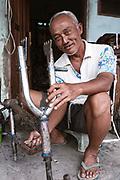 An elderly man works on fixing bikes up in Yogyakarta.