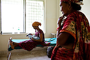Laxmi Oli, 23, cradles her 3-day-old 2nd child, as her mother-in-law looks on in the Bardia District Hospital one hour's walk from her village in Bardia, Western Nepal, on 29th June 2012. Laxmi had her first child at 18. In Bardia, StC works with the district health office to build the capacity of female community health workers who are on the frontline of health service provision like ante-natal and post-natal care, and working together against child marriage and teenage pregnancy especially in rural areas. Photo by Suzanne Lee for Save The Children UK
