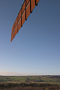 """Angel of the North is a modern sculpture designed by Antony Gormley in 1994, which is located in Gateshead, United Kingdom. As the name suggests, it is a steel sculpture of an angel, standing 66 feet (20 metres) tall, with wings measuring 178 feet (54 metres) across ? making it wider than the Statue of Liberty's height. The wings themselves are not planar, but are angled 3.5 degrees forward, which Gormley has said aims to create """"a sense of embrace"""". It stands on a hill, on the southern edge of Low Fell overlooking the A1 road and the A167 road into Tyneside and the East Coast Main Line rail route. It has now come to be considered by some as a landmark for the North East of England and is one of the 12 official 'Icons of England'."""