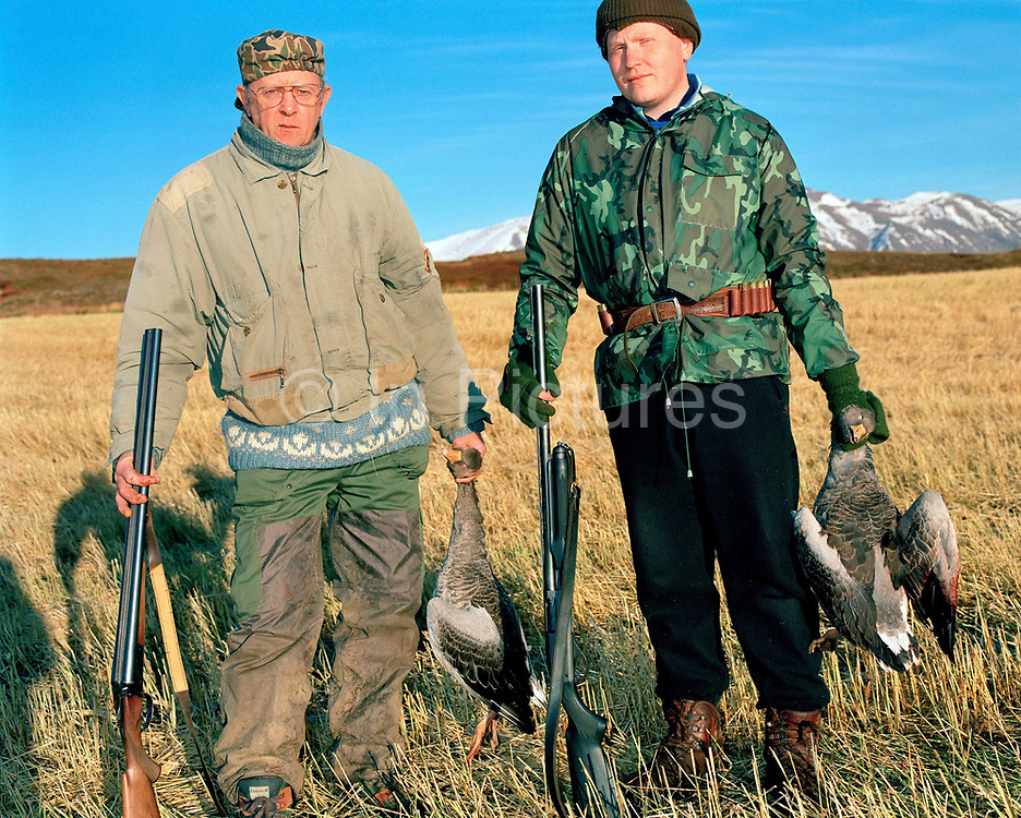 Portrait of an Icelandic farmer and his son holding greglag geese they have shot in their fields, Dalvik, Iceland