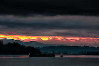 Dynamic Distant Sunrise: Under ominously heavy clouds, a lone tug boat tows a barge down the Fraser River towards a distant mountain range and a most dynamic sunrise, Fort Langley, British Columbia Canada.