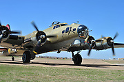 """John """"Lucky"""" Luckadoo, a World War II bomber pilot, poses for a portrait next to a Boeing B-17G Flying Fortress outside the Frontiers of Flight Museum in Dallas on Wednesday, March 20, 2013. (Cooper Neill/The Dallas Morning News)"""