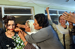 KABUL,AFGHANISTAN - AUGUST 29: An Afghan bride's mother and grandmother put in an earring during an engagement ceremony, August 30, 2002 in Kabul, Afghanistan. The bride is given earrings, a necklace, rings and other gold jewelry along with new clothes and shoes during the ceremony.  Each Friday, every beauty salon is filled with  brides, the hotels are jammed with young couples and most streets are packed with streams of cars, blaring their horns as Afghans rush to get married after decades of war. (Photo by Ami Vitale/Getty Images)