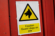 Caution guard dogs on site sign in London, England, United Kingdom.