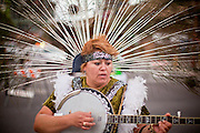 """03 DECEMBER 2011 - PHOENIX, AZ:    A woman dances and plays banjo during a procession to honor the Virgin of Guadalupe in Phoenix Saturday. The Phoenix diocese of the Roman Catholic Church held its Sixth Annual Honor Your Mother Day Saturday to honor the Virgin of Guadalupe. According to Mexican Catholic tradition, on December 9, 1531 Juan Diego, an indigenous peasant, had a vision of a young woman while he was on a hill in the Tepeyac desert, near Mexico City. The woman told him to build a church exactly on the spot where they were standing. He told the local bishop, who asked for some proof. He went back and had the vision again. He told the lady that the bishop wanted proof, and she said """"Bring the roses behind you."""" Turning to look, he found a rose bush growing behind him. He cut the roses, placed them in his poncho and returned to the bishop, saying he had brought proof. When he opened his poncho, instead of roses, there was an image of the young lady in the vision. The Virgin is now honored on Dec 12 in Catholic churches throughout Latin America and in Hispanic communitied in the US. PHOTO BY JACK KURTZ"""
