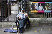 An elderly gent confined to a wheelchair plays melodies in his violin outside the National Portrait Gallery, near music poster. Sitting in his vehicle with its breaks set on, the man sits playing the sweet melodies that any passer-by chooses in return for a few coins. On the posters attached to the gallery railings are the faces of inventor Sir James Dyson, the singer George Michael and an unknown fellow violinist.