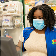 A mask wearing cashier rings up groceries behind a newly installed protective plastic shield attached to the cash register at Fancy Fruit and Produce grocery store on Friday, April 3, 2020 in Orlando, Florida. (Alex Menendez via AP)