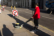 Cleaner in the city on a quiet weekend manoeuvres his floor polishing machine across the pavement. It looks weird as if he's cleaning the street. London, UK.