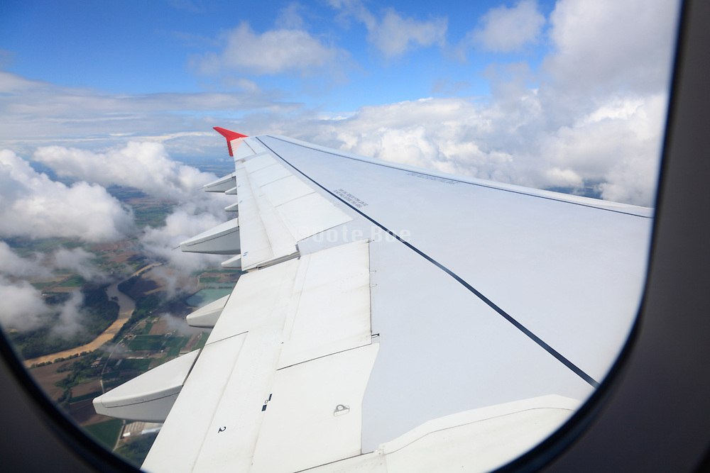 wing of an airplane that is going up with clouds and land
