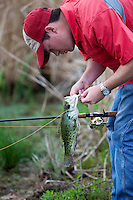 ANGLER IN A FARM POND TAKING A CRAPPIE OFF OF A BAITCASTING RIG AFTER CATCHING IT WITH A WHITE SPINNERBAIT