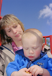 Single mother sitting on climbing frame in playground with young son,