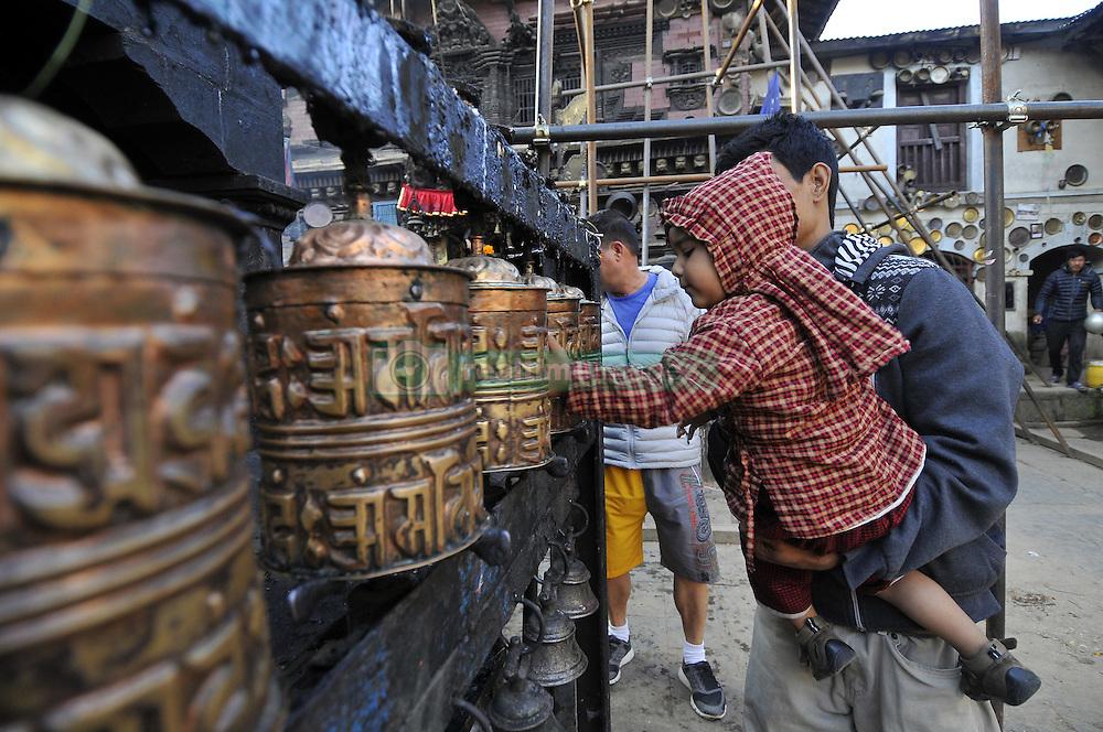 October 19, 2016 - Kathmandu, NP, Nepal - A Kid helps by his father to rotate ritual prayer wheel at the premises of Adinath Temple during a month Adinath Mela festival in Chobhar, Kirtipur, Kathmandu, Nepal on Wednesday, October 19, 2016. In the month of October or November from Kojagrat purnima to Kartik purnima for a month, people visit Adinath temple in the morning and perform special rituals puja and ritual function during Adinath Mela. (Credit Image: © Narayan Maharjan/NurPhoto via ZUMA Press)