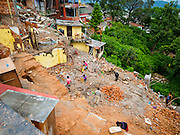 31 JULY 2015 - KATHMANDU, NEPAL: Workers recover bricks and building materials to be recycled and reused from a Buddhist monastery at Swayambhunath, also known as the Monkey Temple. Two monks were killed when the monastery was destroyed by the earthquake. Swayambhunath is a complex of Buddhist and Hindu temples in Kathmandu. It was heavily damaged in the Nepal Earthquake. The Nepal Earthquake on April 25, 2015, (also known as the Gorkha earthquake) killed more than 9,000 people and injured more than 23,000. It had a magnitude of 7.8. The epicenter was east of the district of Lamjung, and its hypocenter was at a depth of approximately 15 km (9.3 mi). It was the worst natural disaster to strike Nepal since the 1934 Nepal–Bihar earthquake. The earthquake triggered an avalanche on Mount Everest, killing at least 19. The earthquake also set off an avalanche in the Langtang valley, where 250 people were reported missing. Hundreds of thousands of people were made homeless with entire villages flattened across many districts of the country. Centuries-old buildings were destroyed at UNESCO World Heritage sites in the Kathmandu Valley, including some at the Kathmandu Durbar Square, the Patan Durbar Squar, the Bhaktapur Durbar Square, the Changu Narayan Temple and the Swayambhunath Stupa. Geophysicists and other experts had warned for decades that Nepal was vulnerable to a deadly earthquake, particularly because of its geology, urbanization, and architecture.        PHOTO BY JACK KURTZ