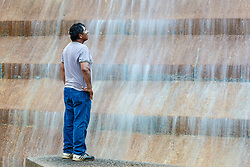 Man exploring the Active Pool at Fort Worth Water Gardens, Fort Worth, Texas, USA.