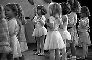 Three and four year-old girls clap their hands during a Saturday morning ballet dance group in south London. Using selective focus, we see more clearly a young ballerina dressed in childrens' tou-tou and ballet slippers during this regular Saturday morning dance class in a  church hall near their respective homes.