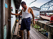 14 NOVEMBER 2017 - BANGKOK, THAILAND: A resident of a riverside community walks back to his home while city workers tear down his neighbors' homes to make way for the city's plan to build a 14 kilometer long (22 mile) riverfront promenade. The city also maintains that the homes interfere with navigation on the river and pose a health a safety hazard because they are prone to seasonal flooding. Thousands of families are expected to be evicted to accommodate the promenade. The riverside communities, built on stilts over the water, are prone to flooding and the city has been trying to control them for years. The houses are the only affordable housing for available to some of the poorest people in Bangkok.  PHOTO BY JACK KURTZ