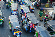 """26 SEPTEMBER 2012 - BANGKOK, THAILAND:  Tuk-tuks (three wheeled taxis) wait for fares at an exit to Khlong Toey Market in Bangkok. Khlong Toey (also called Khlong Toei) Market is one of the largest """"wet markets"""" in Thailand. The market is located in the midst of one of Bangkok's largest slum areas and close to the city's original deep water port. Thousands of people live in the neighboring slum area. Thousands more shop in the sprawling market for fresh fruits and vegetables as well meat, fish and poultry.    PHOTO BY JACK KURTZ"""