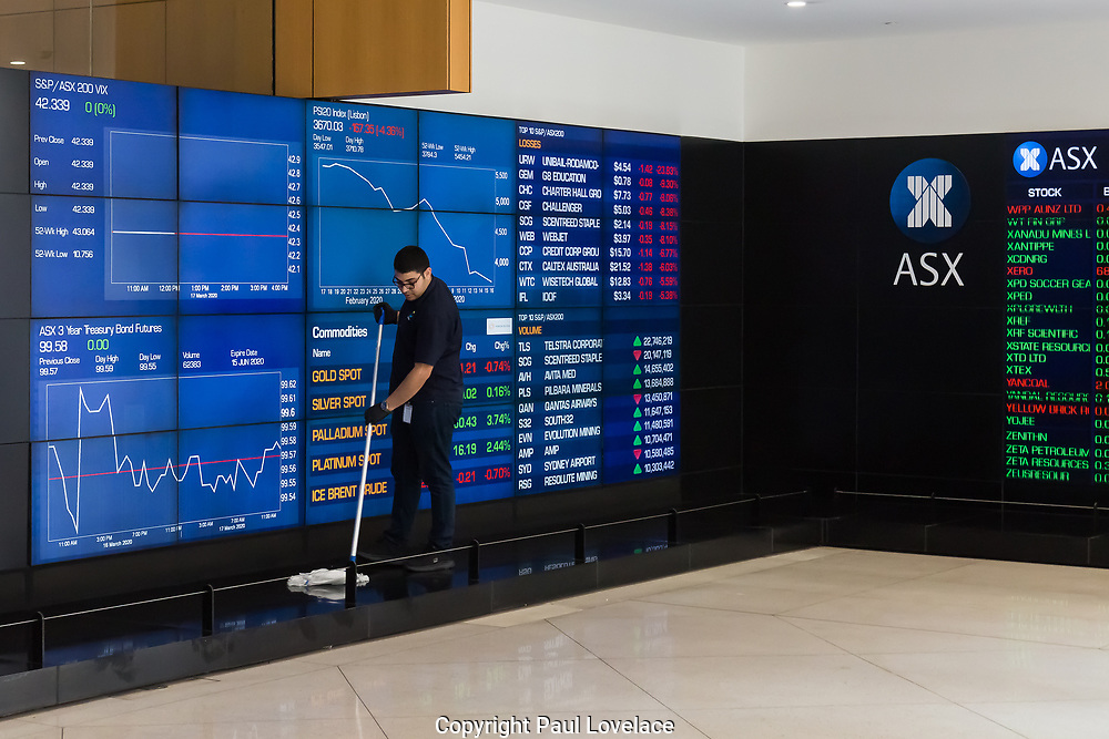 Australian Securities Exchange in Sydney's Central Business District is very empty as a result of the Coronavirus Outbreak, with very few office workers around, Sydney, Australia. A cleaner disinfecting the floor area.