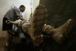 Members of Company C, 407th Forward Support Battalion, 82nd Airborne Division, known as the Charlie Med, treat Spc. Timothy McVay, Baghdad, Iraq, Aug. 10, 2003. McVay  was injured when a piece of shrapnel punctured his arm after an Improvised Explosive Device exploded while on patrol.