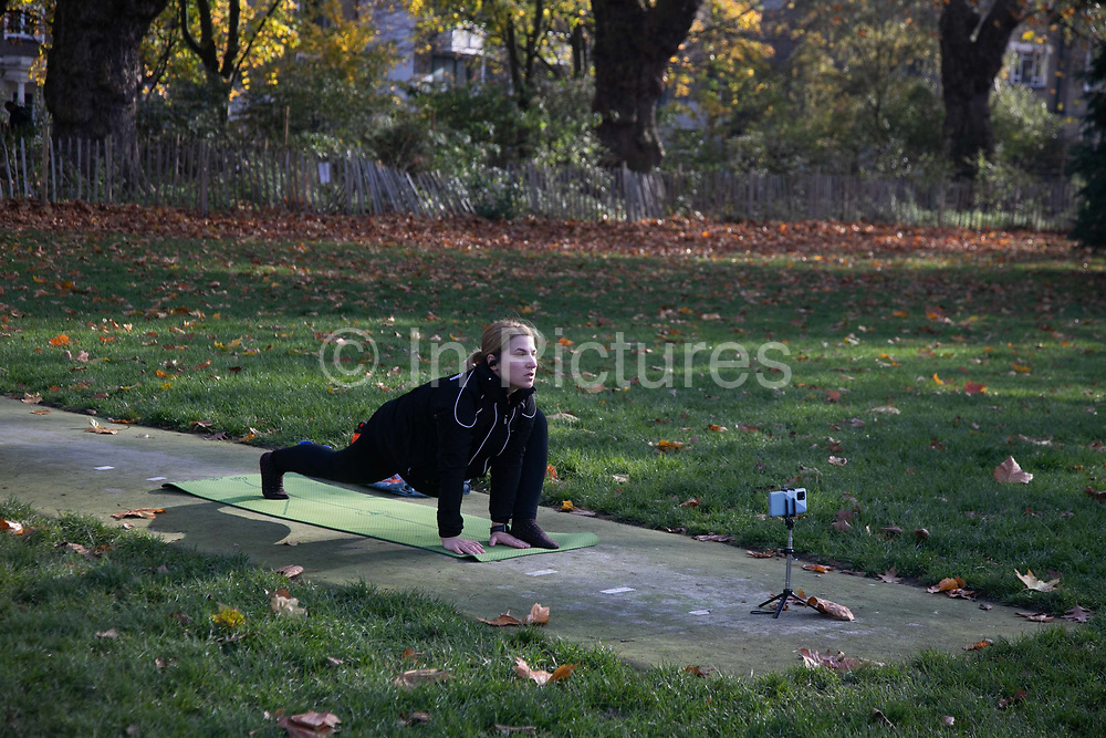 A woman exercises in front of a camera in London Fields during the second coronavirus national lockdownon on 7th of November 2020, Hackney, East London, United Kingdom. London Fields is used by many for exercise and socializing, especially in the time of lockdown. The UK Government introduced a 4 week lockdown from November 5th - December 2nd to combat the coronavirus outbreak. It is the third day of the national lockdown restrictions mean that people are only allowed to meet outside, in pairs and only if keeping social distance. Only if they already live together or have formed a social bubble can they interact freely.