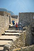 Hikers exploring Machu Piccchu's architecture, Cusco Region, Urubamba Province, Machupicchu District in Peru, South America