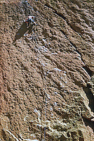 A man rock climbing on a vertical rock wall<br />
