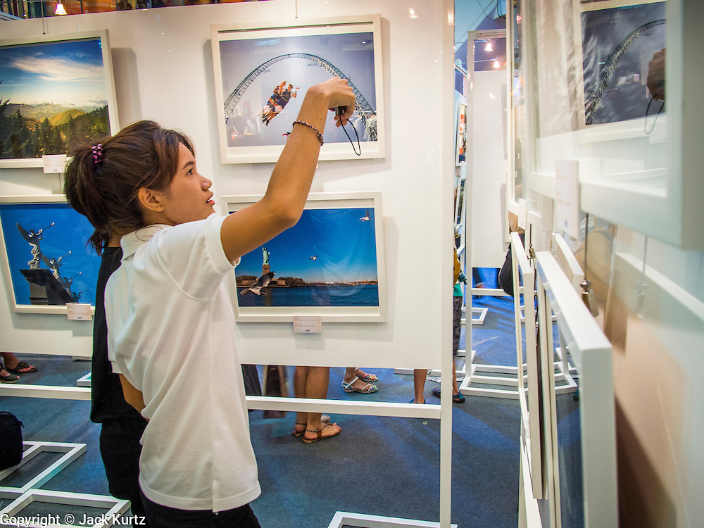 19 JULY 2013 - BANGKOK, THAILAND:   A Thai woman takes a picture of a photo hanging in a photo exhibit in CentralWorld in Bangkok. The US Embassy in Bangkok sponsored the photo exhibit, which celebrates 180 years of US-Thai diplomatic relations. There are 180 photos hanging in the show, 90 by American photographers in Thailand and 90 by Thai photographers in the United States. The show, which opened July 19, is hanging in CentralWorld, a large mall in Bangkok, and is touring Thailand when it concludes its Bangkok run on July 21.   PHOTO BY JACK KURTZ