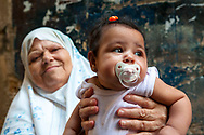 Sidon, Lebanon - September 24, 2010: A woman holds her granddaughter in the old city of Sidon, Lebanon. Pacifier made in Germany.