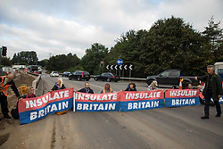 Insulate Britain climate activists block a slip road from the M25 at Junction 25 as part of a campaign intended to push the UK government to make significant legislative change to start lowering emissions on 15th September 2021 in Enfield, United Kingdom. The activists, who wrote to Prime Minister Boris Johnson on 13th August, are demanding that the government immediately promises both to fully fund and ensure the insulation of all social housing in Britain by 2025 and to produce within four months a legally binding national plan to fully fund and ensure the full low-energy and low-carbon whole-house retrofit, with no externalised costs, of all homes in Britain by 2030 as part of a just transition to full decarbonisation of all parts of society and the economy.
