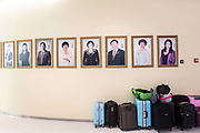 Suite cases stand under photographs of sales representatives at the Tiens Group headquarters in Tianjin, China on Tuesday, Aug. 9, 2016. Tiens is a direct sales firm specializing in health and beauty products.