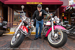 "Dale Aure of Montrose, Colorado on Main Street in Deadwood with two bikes he's built; a 1965 last year Panhead (1st year electric start) in original optional color ""HiFi Red"" trim and a 1966 1st year Shovelhead in original optional color ""Sparkling Burgundy"". Shot during the Sturgis Black Hills Motorcycle Rally, USA. Friday, August 9, 2019. Photography ©2019 Michael Lichter."