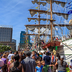 Baltimore, MD, USA - June 16, 2012: Visitors walk past large ships in the Inner Harbor of the City of Baltimore, Maryland.