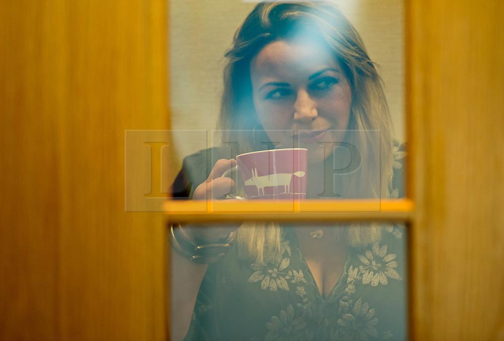 © Licensed to London News Pictures. 04/06/2015. Singer and activist CHARLOTTE CHURCH seen through the glass in a doorway, drinking a cup of tea before taking part in a panel press conference at the Unite Union building in London, ahead of an anti-austerity demonstration on June 20th. London, UK. Photo credit: Ben Cawthra/LNP