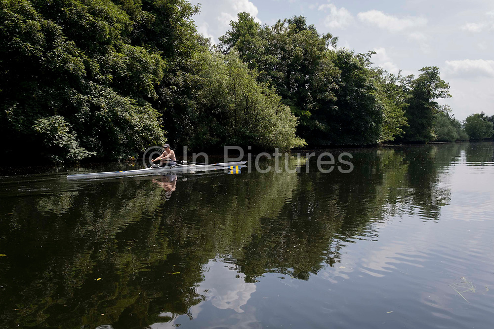 A single-scull rower powers his way along a calm River Yare near Norwich, on 2nd July 22021, in Norwich, England.