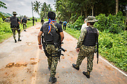 08 JULY 2013 - MAYO, PATTANI, THAILAND:  Thai security personnel walk up to the scene of an IED blast in Pattani Monday after the scene was cleared by the bomb squad. Eight Thai soldiers were injured - one seriouly and seven with minor injuries - when their truck was hit by an IED outside Mayo, Pattani province in southern Thailand Monday. The soldiers were returning from a teacher protection mission when their truck ran over the explosive. The attack was thought to be conducted by Muslim insurgents who have been battling the Thai government for greater autonomy. The conflict in southern Thailand has claimed about 5,000 lives since 2004.   PHOTO BY JACK KURTZ