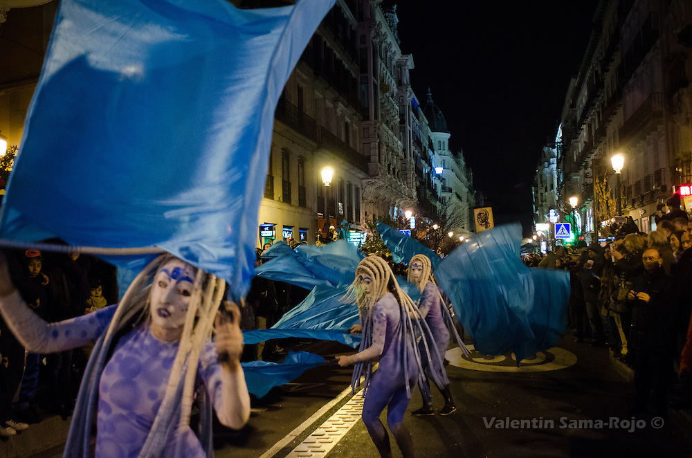 Women dressed as jellyfishes dancing with blue flags as the sea at Mayor Street during Madrid's carnival parade. They are part of Carros de Foc group.