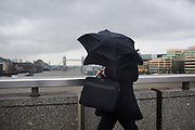 A man struggles with his umbrella in the rain and wind crossing London Bridge 2nd February 2016.