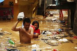 February 6, 2018 - Jakarta, Indonesia - Residents evacuate their goods during the massive flood that hit the low settlements in Jakarta. Information Data Center and Public Relations of the National Disaster Prevention Agency (BNPB) will reach the Manggarai Water Gate, Jakarta. The flood is predicted to flood the river banks such as Srengseng Sawah, Rawajati, Kalibata, Pengadegan, Pejaten Timur, Kebon Baru, Bukit Duri, Balekambang, Cililitan, Chinese Bidara and Kampung Melayu, caused by heavy rain and high river water flow from Bogor to Jakarta. Edi Ismail  (Credit Image: © Edi Ismail/NurPhoto via ZUMA Press)