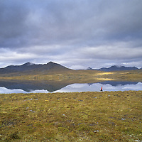A woman runs in tundra by a remote lake in the Logan Mountains, Yukon Territory, Canada