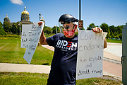 "24 JULY 2020 - DES MOINES, IOWA: RYAN BARCUS, a special education teacher from Ankeny, IA, stands on the grounds of the State Capitol and cheers teachers driving around the capitol. Hundreds of teachers from across Iowa came to the state capitol Friday to protest Governor Kim Reynolds' order that school must reopen with in person education and minimized the potential for ""distance learning."" The event was one of the largest COVID-19 protests in Iowa since the pandemic started, more than 740 teachers signed up to attend the protest. After the protest officially ended, many teachers left the capitol and drove to Gov. Reynolds' residence, where they drove around her mansion and honked horns. Some people left notes on the entrance to the governor's residence. Gov. Reynolds ordered the school reopening last week, but according to teachers, the state has not implemented health guidelines or bought protective equipment like face masks in the quantity required to slow the spread of the Coronavirus (SARS-CoV-2). Iowa's numbers of COVID-19 infections are up statewide.         PHOTO BY JACK KURTZ"