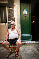 An elderly man sitting in Vernazza, Italy.
