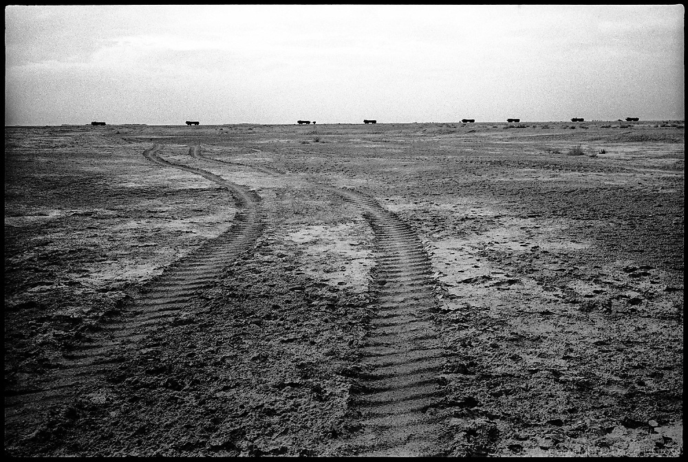 Tired tracks in the desert near Al-Musayab, Iraq, with an American military convoy passing in the background. Once scarred, the desert surface keeps many marks until they are casually destroyed by the amateur grave diggers who exhumed the mass graves around Iraq.
