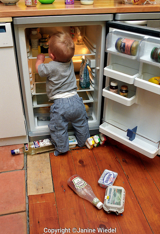 Toddler emptying the icebox.