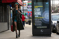 © Licensed to London News Pictures. 25/12/2020. London, UK. A woman walks past the government's 'Stay Home- Tier 4' publicity campaign poster in north London amid fears of a third national lockdown after Christmas as COVID-19 infection rates rise. Many more areas of England will go into Tier 4 restrictions from Boxing Day as the mutated strains continue to spread throughout England. Photo credit: Dinendra Haria/LNP