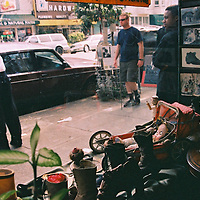 1. When was this photo taken?<br /> <br /> Probably around 2001-2002.<br /> <br /> 2. Where was this photo taken?<br /> <br /> From inside a cobbler's shop, upper Haight, San Francisco.<br /> <br /> 3. Who took this photo?<br /> <br /> I did.<br /> <br /> 4. What are we looking at here?<br /> <br /> Out of this little shop, one of the few cobbler businesses left (as I recall, the owner was from El Salvador), onto Haight St. I was waiting in line to inquire about having some shoes resoled.<br /> <br /> 5. How does this old photo make you feel?<br /> <br /> Nostalgic and sad that small businesses like this are fading out. I felt the history in that overcrowded nook, totally disorganized from my side of the counter, but knowing it was all a well-oiled machine. He had pride he in his craftsmanship and was so friendly. He retired in his 80s and the business wasn't passed on. From what I have read, the business was a cobbler for about 90 years. <br /> <br /> 6. Is this what you expected to see?<br /> <br /> No. I had no idea! Just a normal day, which is what I love to document. Change is the only constant, which is why I often keep my camera handy for those mundane moments. It's not always the big moments.<br /> <br /> 7. What kind of memories does this photo bring back? <br /> <br /> Walking, wandering with the camera. Always paying attention to detail and little visual nuggets. What I truly enjoy is how these time stamps in image form can trigger the memory. I am brought back immediately upon seeing this, just an insignificant moment. I can smell the leather and tools in the shop. I can hear the street sounds of people passing and the 71 Haight bus line.<br /> <br /> 8. How do you think others will respond to this photo?<br /> <br /> They may relate if they are in a place that still has a neighborhood cobbler and lament that cobblers are becoming less relevant in the Internet and fast-fashion era. They may be younger and have never have thought of having quality shoes t