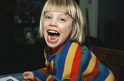 Young girl laughing with mouth wide open,