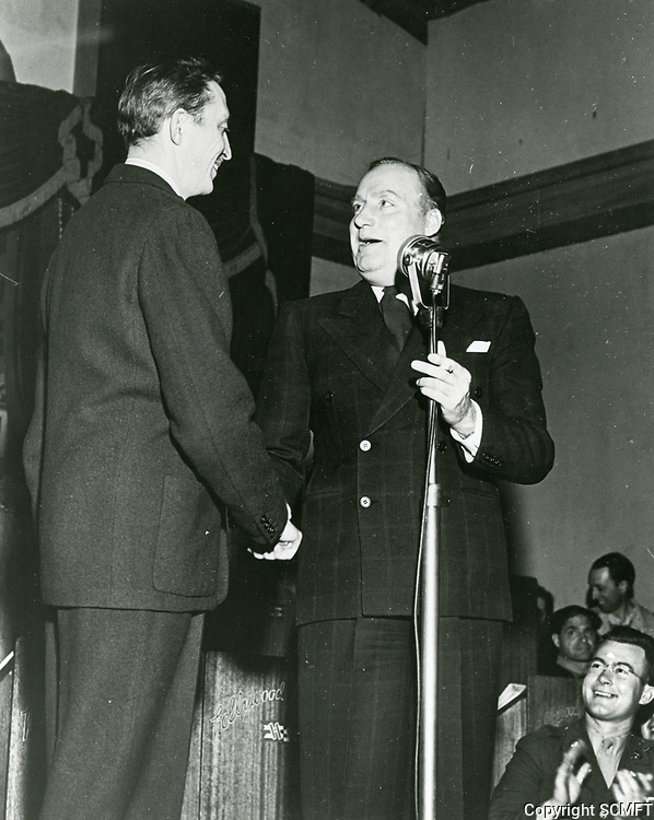 1944 Alan Mobray shakes hands with Mischa Auer on stage at the Hollywood Canteen