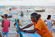 Boat owner fisherman waiting for more business. February 2nd is the feast of Yemanja, a Candomble Umbanda religious celebration, where thousands of adherants visit the Rio Vermehlo Red River to make offerings of flowers and prayers, paying their respects to Yemanja, the Orixa goddess of the Sea and water.